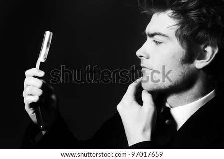 low key image of a young man holding a cut throat razor what could his intentions be
