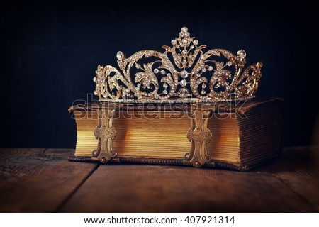 low key image of beautiful diamond queen crown on old book. vintage filtered. selective focus. medieval period concept - stock photo
