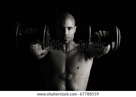 Low key image of fitness man with weights - stock photo