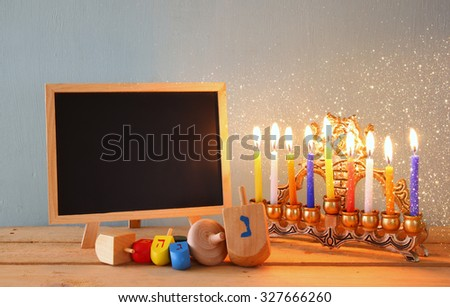 low key image of jewish holiday Hanukkah with menorah (traditional Candelabra) and wooden dreidels spinning top with chalkboard background, room for text  - stock photo