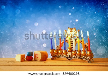 low key image of jewish holiday Hanukkah with menorah (traditional Candelabra) and wooden dreidels (spinning top). glitter background  - stock photo