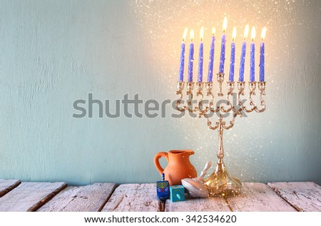 low key image of jewish holiday Hanukkah with menorah (traditional Candelabra) and wooden dreidels (spinning top). glitter overlay  - stock photo