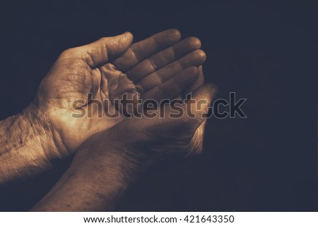 low key image of male Wrinkled old hands begging asking for money, help, reaching out and compassion concept. sepia style filtered - stock photo