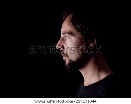 Low key image of the profile of a bearded man