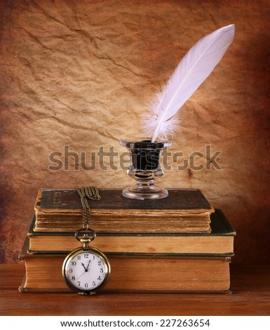 low key image of white Feather, inkwell and ancient books on old wooden table - stock photo