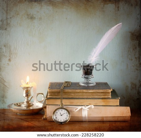 low key image of white Feather, inkwell and ancient books on old wooden table.
