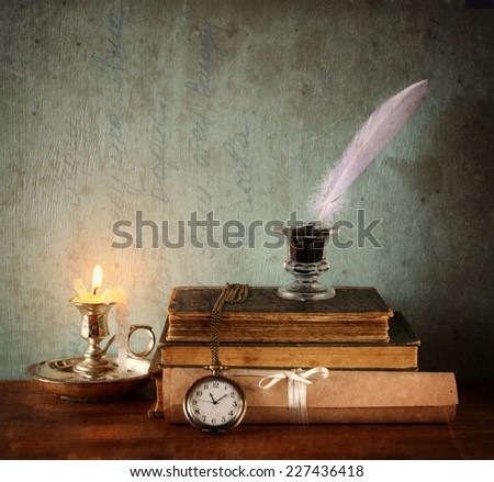 low key image of white Feather, inkwell, candle and old books on  wooden table. image filtered and  textured - stock photo