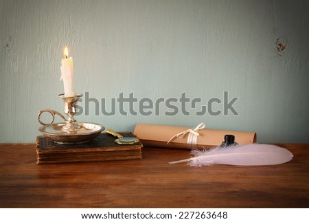 low key image of white Feather, inkwell, scroll ancient book on old wooden table - stock photo