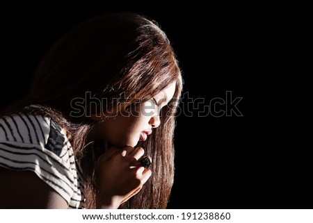 Low key image of young girl praying   - stock photo