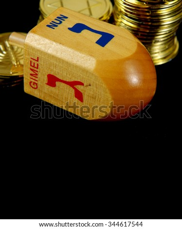 Low key image with side lighting of Hanukkah dreidel and gelt. Objects are on a rough, black background. The gelt has seasonal images of the Star of David and a menorah. Narrow depth of field. - stock photo