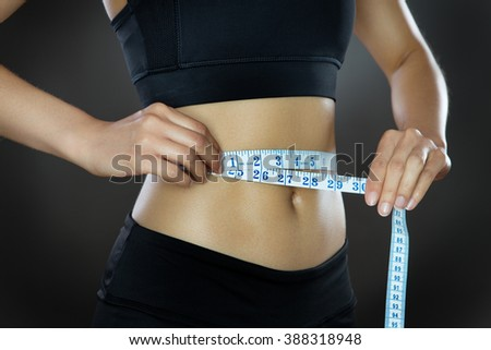 low key lighting close up shot of a woman's midriff using a tape measure around her waist - stock photo