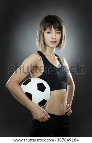 low key lighting of a woman holding a english football shot in the studio on a gray background