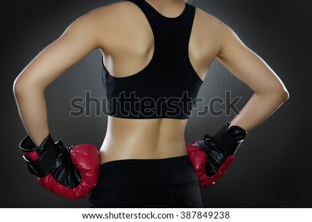 low key lighting of a woman's from the back wearing boxing gloves shot in the studio on a gray background - stock photo