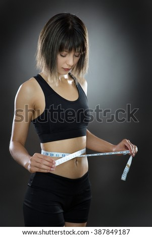 low key lighting of a woman using a tape measure around her waist