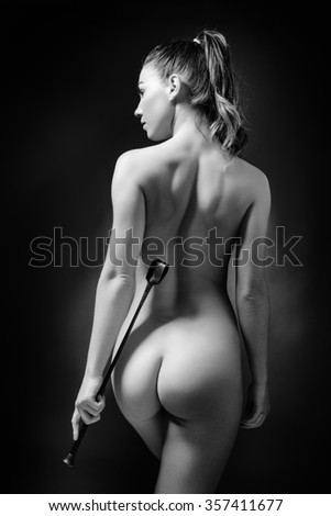 low key lighting of the back of a sexy woman holding a whip
