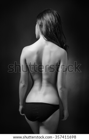 low key lighting of the back of a sexy woman wearing knickers