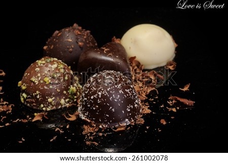 Low Key lighting on a selection of premium chocolates, on a reflective background and shallow DOF, with space for text - stock photo