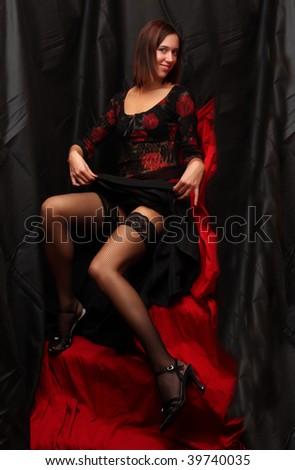 Low key lighting studio shot young beautiful women on red background - stock photo