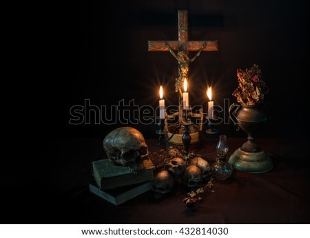 Low key of antique crafted crucifixion on crafted wooden cross with lit candles and skulls foreground - stock photo