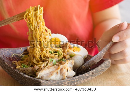 Low key of image of woman eating  Meat Noodle with egg in a bowler bowl on wooden background. Thai Noodle small line with pork and meat ball. Favorite meal for lunch. Thailand food.