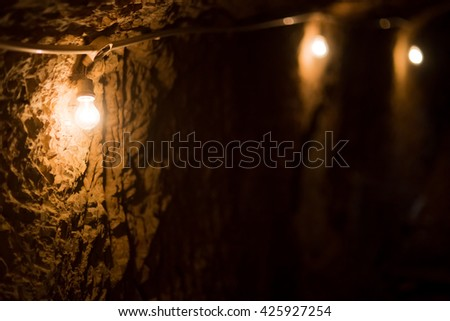 Low key photo of room in a cave with lamp - stock photo