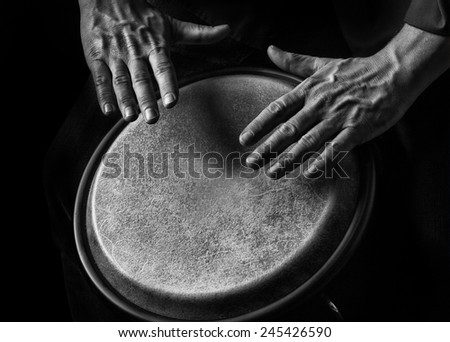 Low key picture  of a bongo Player. Black background .Detail  shot Picture is toned. - stock photo