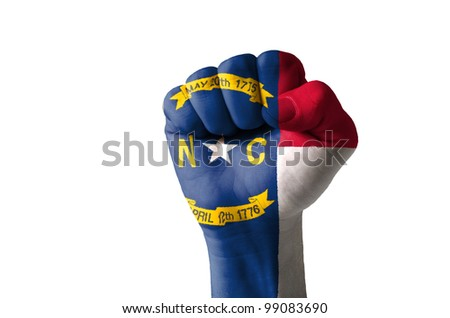 Low key picture of a fist painted in colors of american state flag of north carolina