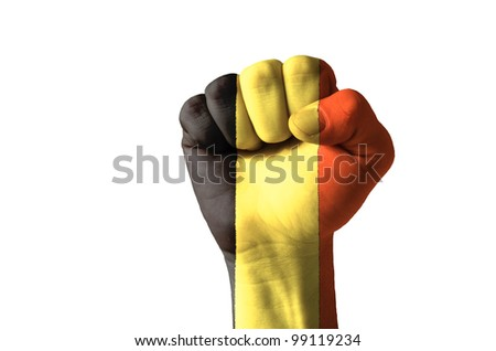 Low key picture of a fist painted in colors of belgium flag - stock photo