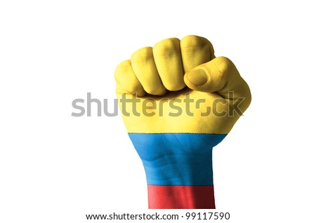 Low key picture of a fist painted in colors of colombia flag - stock photo