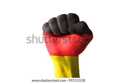 Low key picture of a fist painted in colors of germany flag - stock photo