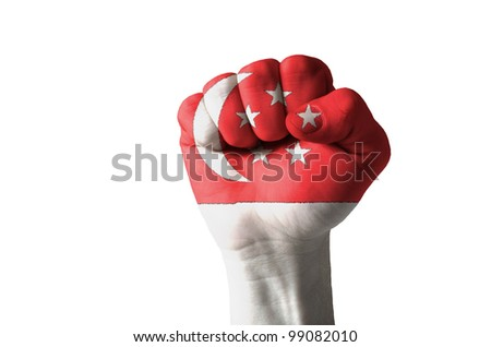 Low key picture of a fist painted in colors of singapore flag - stock photo