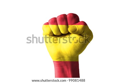 Low key picture of a fist painted in colors of spain flag - stock photo