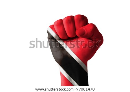 Low key picture of a fist painted in colors of trinidad tobago flag