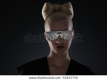 Low key portrait of a beautiful woman in stylish glasses - stock photo