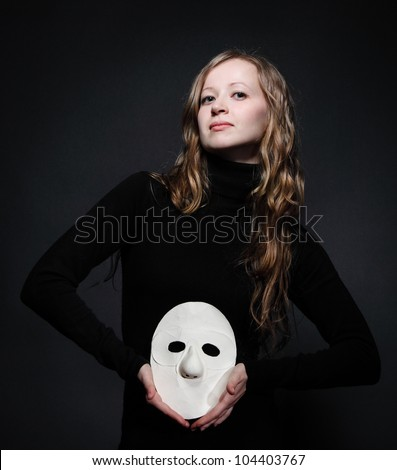 Low key portrait of a beautiful woman with long hair holding mask