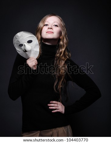 Low key portrait of a beautiful woman with long hair holding mask - stock photo