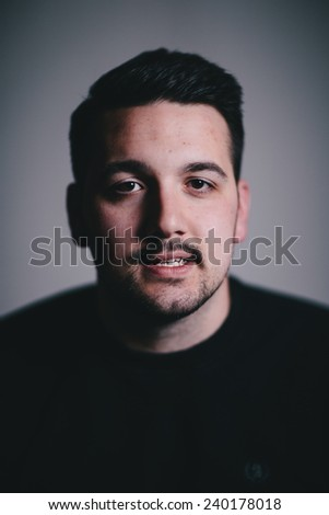 Low key portrait of a serious man in his late twenties slight smile vertical - stock photo