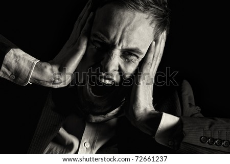 Low-key portrait of desperate businessman in dark suit screaming and holding both hands at head expressing strong despair, isolated on black background with copy-space, black & white conversion.