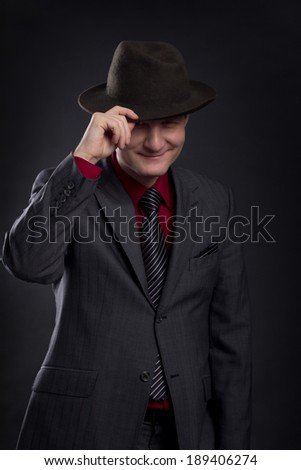 low key portrait of gangster with hat in the darkness