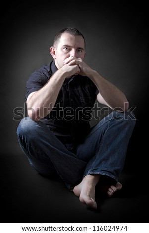 Low key portrait of man sitting in dark and contemplating