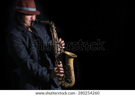 low key portrait of saxophone player on dark,focus on face saxophone player - stock photo