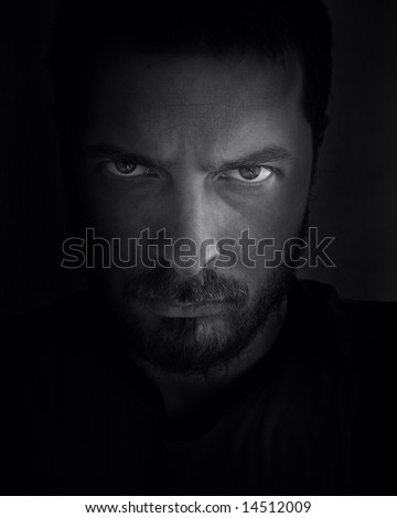 Low-key portrait of scary looking man - stock photo