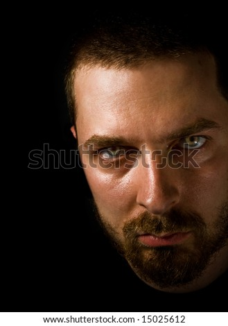 Low-key portrait of sinister man with scary eyes - stock photo