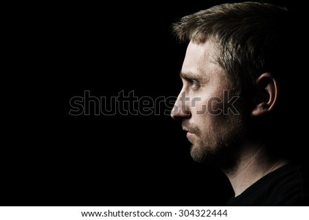 low key portrait of young man - stock photo