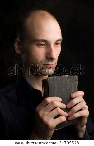 Low key portrait of young man praying - stock photo