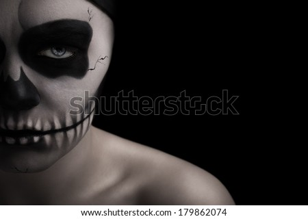 Low key portrait of young woman with skull make-up. - stock photo