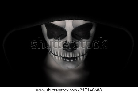 Low key portrait of young woman with skull make-up.