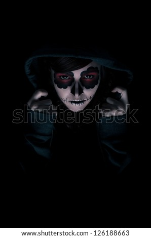 Low key portrait of young woman with sugar skull make-up