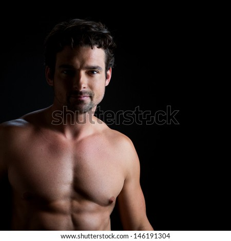 Low key portrait over black of an athletic young man with naked torso, looking directly to the camera. - stock photo