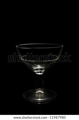 Low key shot of a wine glass against a black background. - stock photo